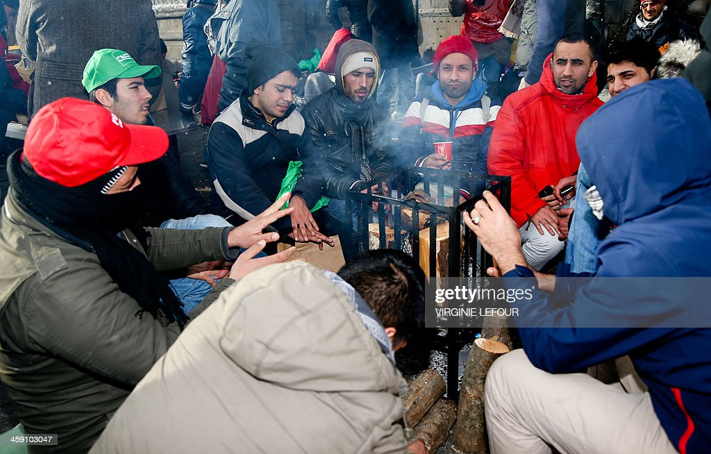 Afghan refugees and Belgian activists warm themselves near a fire as they take part in a protest organized by the 'Afghan Collective', on December 23, 2013, in Mons. Some 200 Afghan asylum-seekers and their supporters set up camp late December 22 in Belgium's western town of Mons, demanding to see Belgian Prime Minister Elio Di Rupo to press for residency papers.