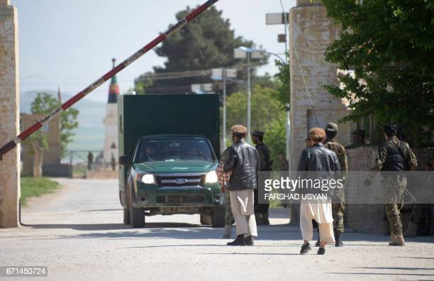 Afghan relatives looks on as an ambulance carrying the bodies of Afghan National army soldiers killed in a Taliban attack arrive in the Dihdadi...