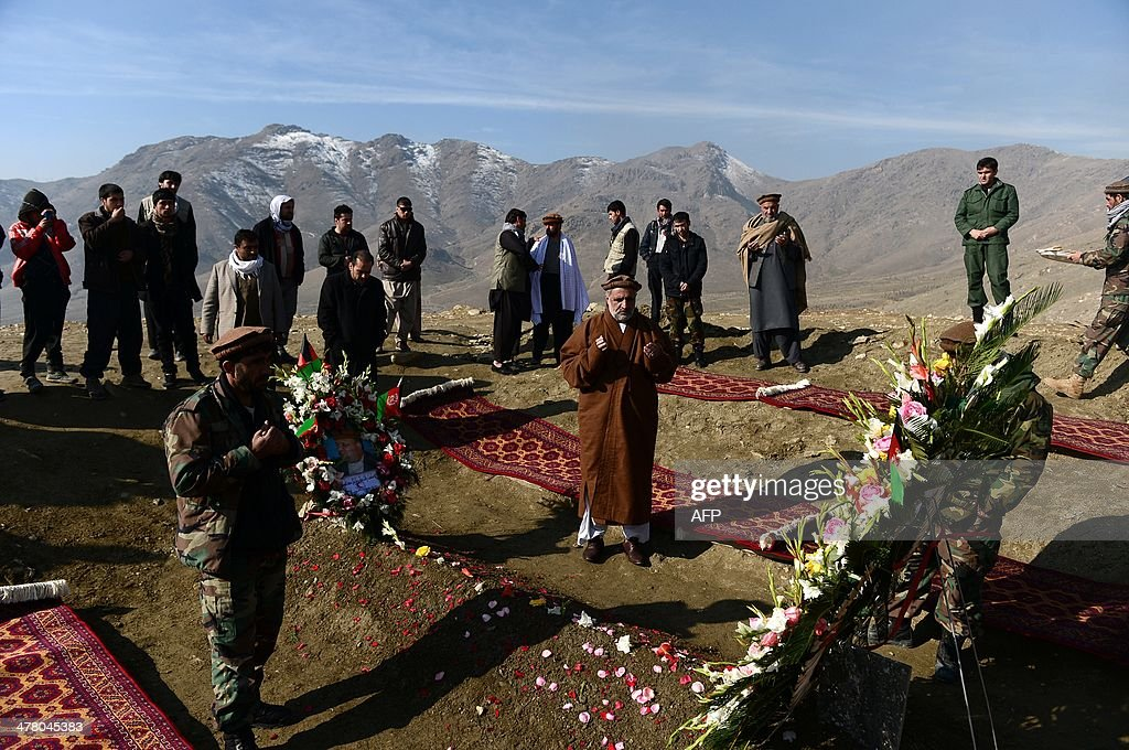 Afghan relatives pray over the grave of Afghan Vice-President Marshal Mohammad Qasim Fahim, formerly one of the country's most feared warlords, at a ceremony in a hilltop in Kabul on March 12, 2014. Afghan Vice-President Marshal Mohammad Qasim Fahim died of natural causes after a turbulent life that reflected the country's recent past. Fahim, a leader of the Tajik ethnic minority, was senior vice-president under President Hamid Karzai, who will step down at elections next month as US-led combat forces pull out of Afghanistan after 13 years of fighting the Taliban. AFP PHOTO/Wakil Kohsar