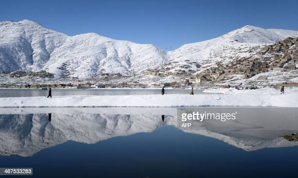 Afghan residents are reflected in the waters of Shuhada Lake in Kabul on February 7 2014 As winter sets in across Central Asia many Afghans struggle...