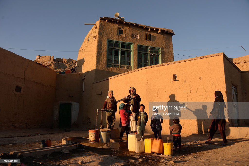 Afghan residents gather around a handpump as they fill containers with water in Ghazni on February 7, 2016. AFP PHOTO / SAYED ZAKERIA / AFP / SAYED ZAKERIA