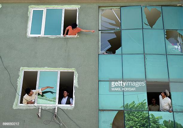 TOPSHOT Afghan residents look out from broken windows of a building near the site of an attack following a car bomb blast that targeted the CARE...