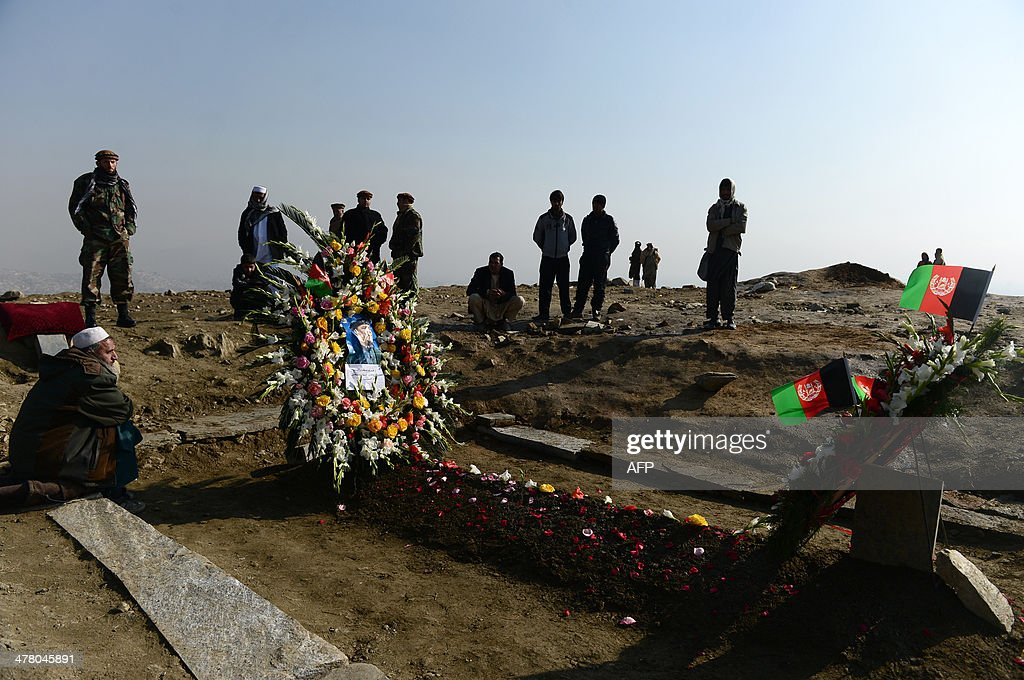 Afghan residents sit beside the gravesite of former Afghan vice-president Marshal Mohammad Qasim Fahim, formerly one of the country's most feared warlords, at a ceremony in a hilltop in Kabul on March 12, 2014. Afghan Vice-President Marshal Mohammad Qasim Fahim died of natural causes after a turbulent life that reflected the country's recent past. Fahim, a leader of the Tajik ethnic minority, was senior vice-president under President Hamid Karzai, who will step down at elections next month as US-led combat forces pull out of Afghanistan after 13 years of fighting the Taliban. AFP PHOTO/Wakil Kohsar