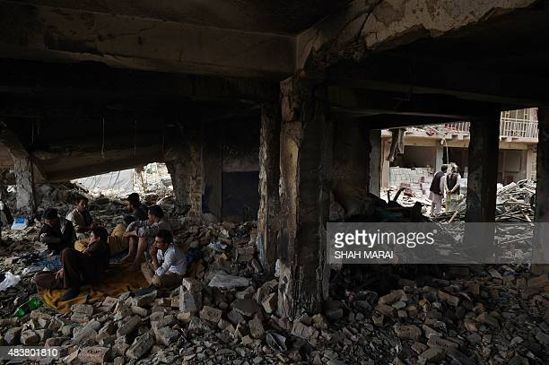 Afghan residents sit under a destroyed building after a powerful truck bomb tore through the centre of Kabul just after midnight in the neighbourhood...