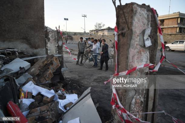 Afghan residents stand near a damaged building near the site of a truck bomb attack in Kabul on May 31 2017 At least 80 people were killed and...