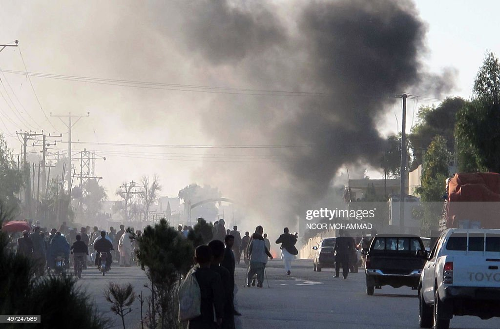 Afghan residents walk as smoke rises from the direction of a suicide bomb attack that targeted foreign military forces in Lashkargah city capital of...