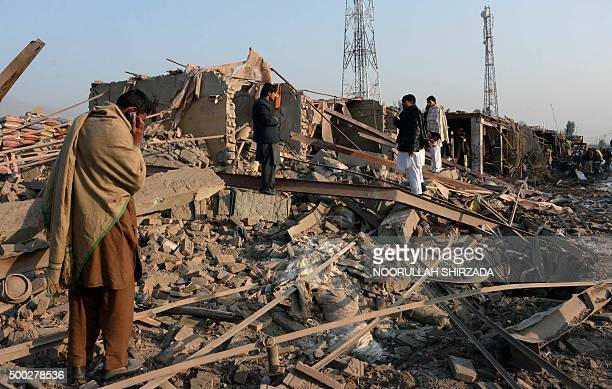 Afghan residents walk past the aftermath of a suicide car bomb attack that targeted the district government compound in Sorkh Rud district of...