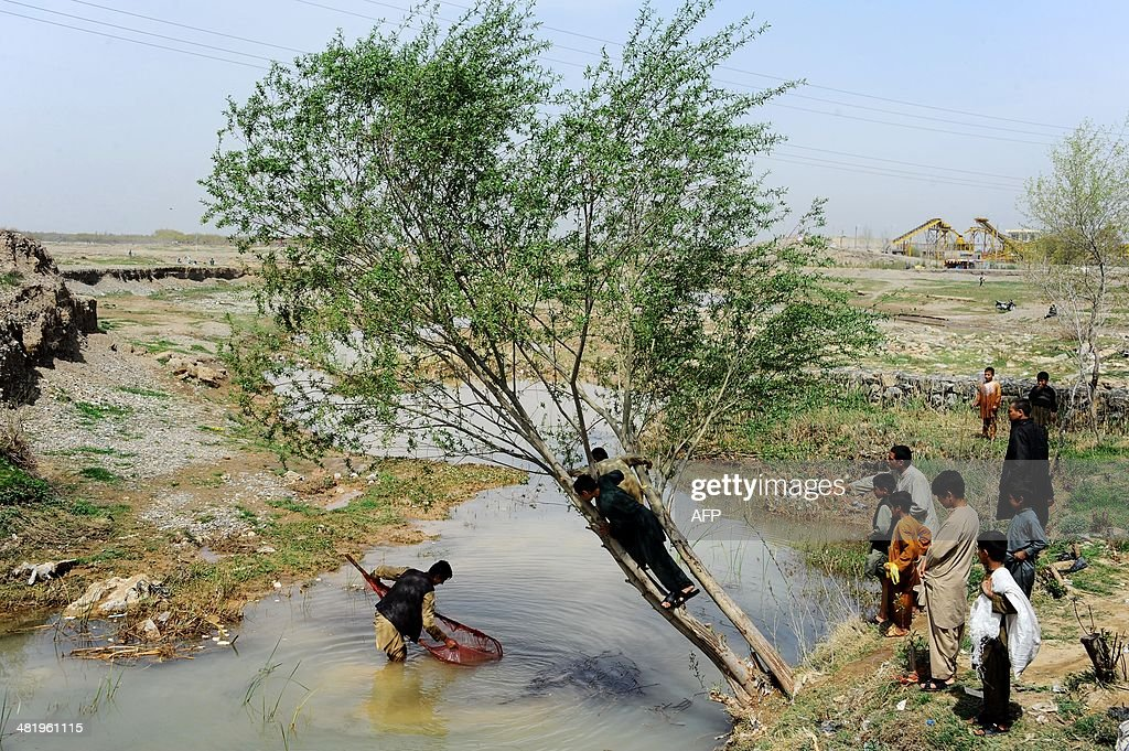 Afghan residents watch a man fishing in the outskirts of the northwestern during 'Sizdeh Bedar' celebrations on the 13th day of Nowruz in the outskirts of the northwestern city of Herat on April 2, 2014. Nowruz is the new year according to the Persian solar calendar and is a Zoroastrian tradition, still celebrated by Iranians, Afghans and Tajiks.