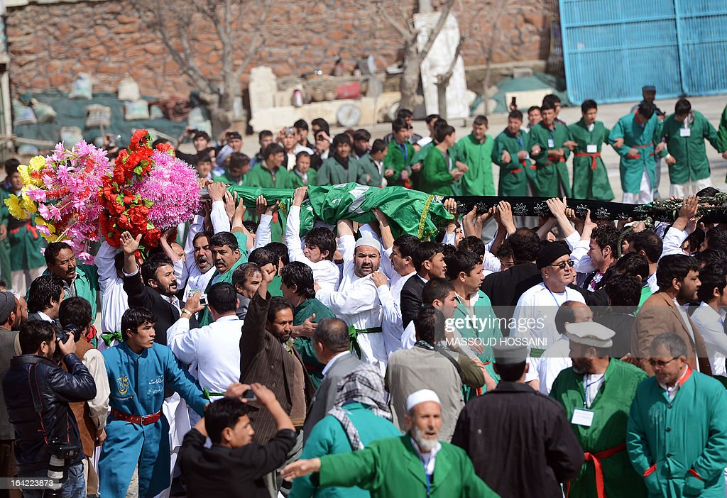 Afghan revellers raise the holy mace at the Sakhi shrine, the centre of the Afghanistan new year celebrations in Kabul during Nowruz festivities on March 21, 2013. Nowruz, one of the biggest festivals of the war-scarred nation, marks the first day of spring and the beginning of the year in the Persian calendar. Nowruz is calculated according to a solar calendar, this coming year marking 1392. AFP PHOTO / Massoud HOSSAINI