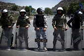 Afghan riot police stand guard as protesters shout antigovernment slogans during a demonstration in Kabul on July 23 2016 Thousands of minority...