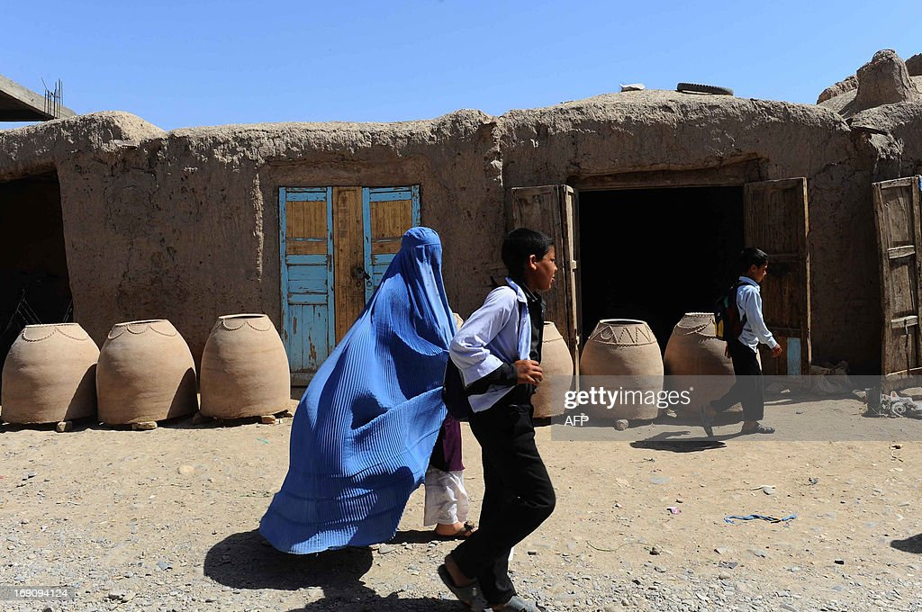 Afghan schollboys and a woman walk past a traditional oven factory in Herat on May 20, 2013. Some nine million Afghans or 36 percent of the population are living in 'absolute poverty' while another 37 percent live barely above the poverty line, according to a UN report. AFP PHOTO/Aref KARIMI