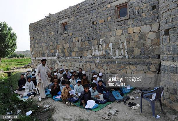 Afghan school children attend classes outside a school building at a village in Sabari district in Khost province in the east of Afghanistan on June...