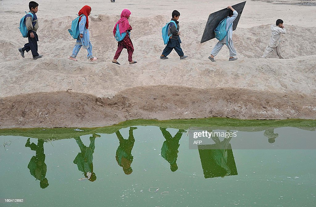 Afghan school children walk home after classes near an open classroom in the outskirts of Jalalabad on January 30, 2013. Afghanistan has had only rare moments of peace over the past 30 years, its education system being undermined by the Soviet invasion of 1979, a civil war in the 1990s and five years of Taliban rule. AFP PHOTO/ Noorullah Shirzada