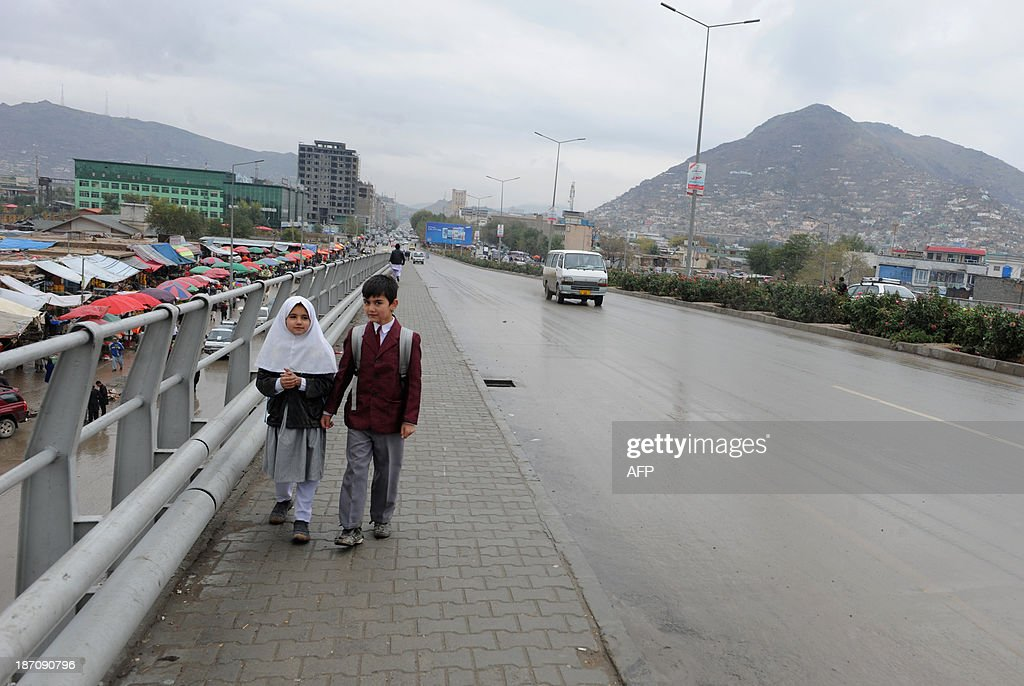 Afghan school children walk home from school on a rainy day in Kabul on November 6, 2013. Despite massive injections of foreign aid since the fall of the Taliban in 2001, Afghanistan remains desperately poor as it attempts to recover from decades of conflict. AFP PHOTO / Farshad USYAN
