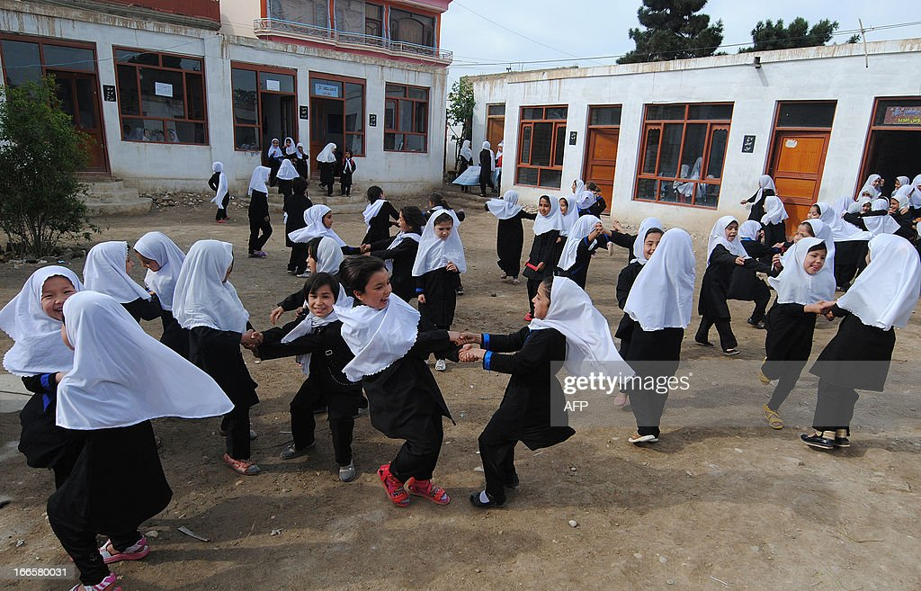 Afghan school girls play in the yard after their class at Ayesha primary school in Mazar-i Sharif on April 12, 2013. Under the hard line Taliban, who ruled Afghanistan between 1996 and 2001, cinema was banned and girls were prohibited from attending school. AFP PHOTO/ Farshad USYAN