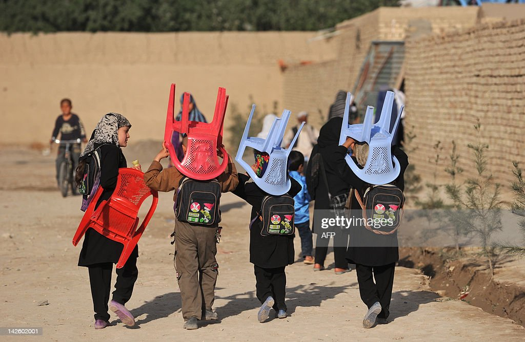 Afghan schoolchildren carry their chairs to a class in an open area in Mazari Sharif capital of the Balkh province on April 9 2012 At the start of...