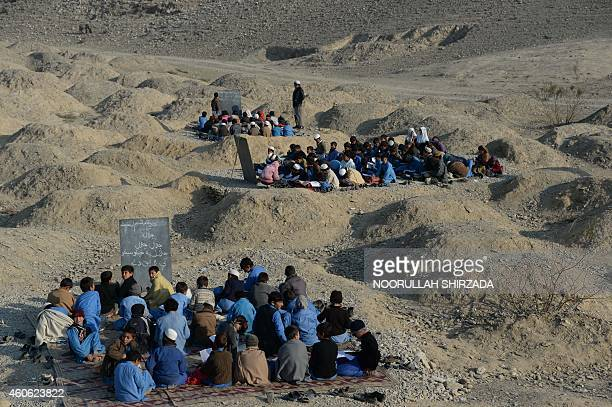 Afghan schoolchildren study at an openair classroom in the Mohmand Dara district in eastern Nangarhar province on December 18 2014 Afghanistan has...