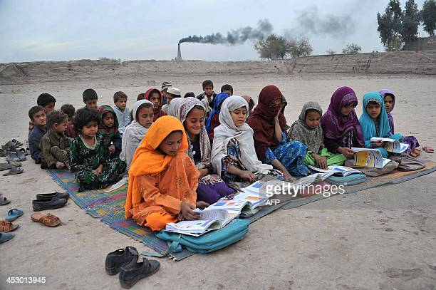 Afghan schoolchildren take lessons in an open classroom at a refugee camp on the outskirts of Jalalabad Nangarhar province on December 1 2013...