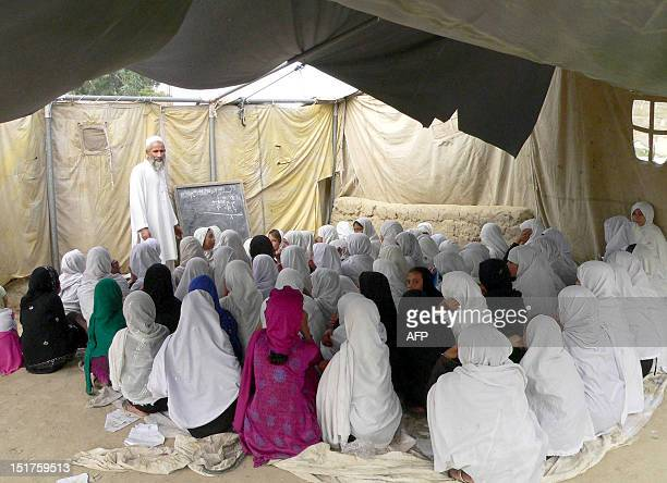 Afghan schoolgirls study in an open air school in the outskirts of Jalalabad on September 11 2012 Violence and abuse against women continues to be a...