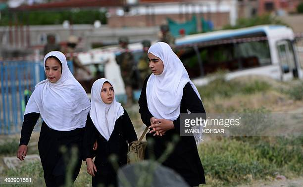 Afghan schoolgirls walk past a damaged military bus after a suicide attack in Kabul on May 26 2014 A Taliban suicide bomber on a motorbike has killed...
