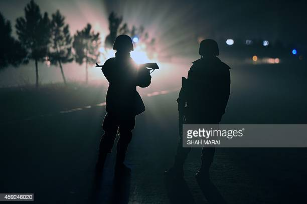 Afghan security force keeps watch as they block a road at the site of suicide car bomb at the gate of Green Village compound a large fortified...