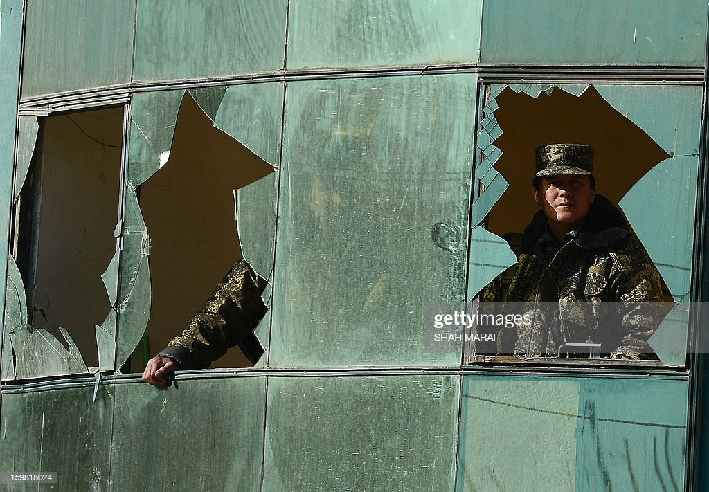 Afghan security force members look through a broken window after a clash between Afghanistan forces and Taliban fighters in Kabul on January 21, 2013. NATO troops joined a fight against a Taliban suicide squad that stormed a Kabul police headquarters at dawn on January 21, killing three police officers and unleashing a stand-off that lasted for more than eight hours. The Taliban claimed the attack, which turned into the longest stand-off between the insurgents and security forces in Kabul since a major co-ordinated raid on the capital lasted 18 hours in April last year. AFP PHOTO/ SHAH Marai
