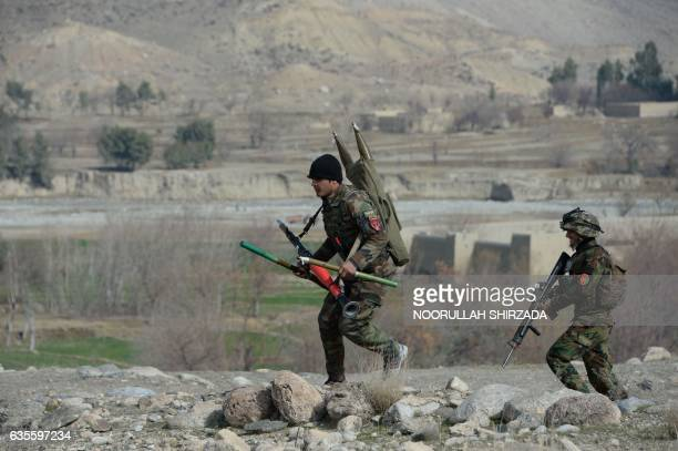 Afghan security force personnel walk during an ongoing an operation against Islamic State militants in Kot district of Nangarhar province on February...