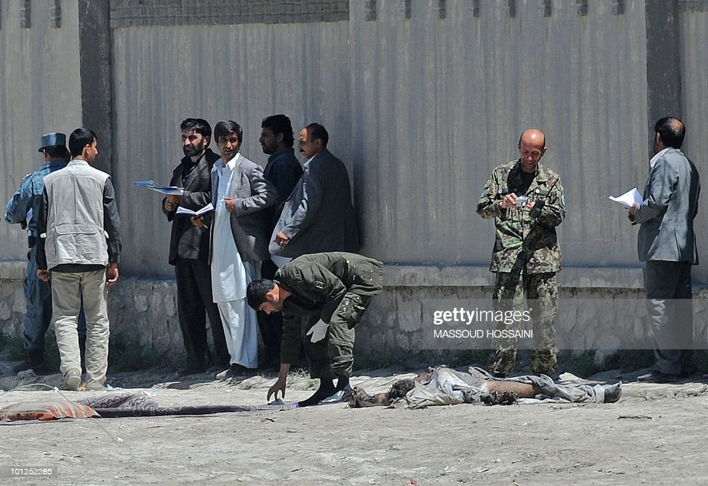 Afghan security forces and officials work at the site of a suicide bomb attack along Kabul-Bagram raod in Kabul on May 29, 2010. A suicide attacker with explosives strapped to his body blew himself up outside a military caterer in Kabul but caused no casualties, Afghanistan's interior ministry said. The explosion took place east of the capital, close to a warehouse and supermarket run by Supreme Food Services, supplier of food to the foreign military, ministry spokesman Zemarai Bashary told AFP. AFP PHOTO/Massoud HOSSAINI