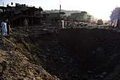 Afghan security forces and residents stand near the crater from a powerful truck bomb in Kabul on August 7 2015 A powerful truck bomb killed at least...
