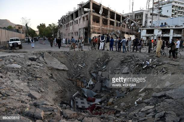 TOPSHOT Afghan security forces and residents stand near the crater left by a truck bomb attack in Kabul on May 31 2017 At least 80 people were killed...