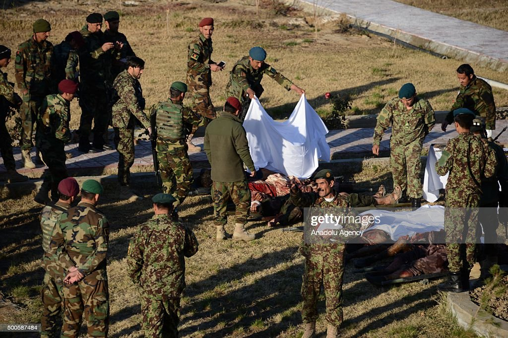 Afghan security forces cover the dead bodies of Taliban militants who were killed during the clashes in an airfield in Kandahar Afghanistan on...