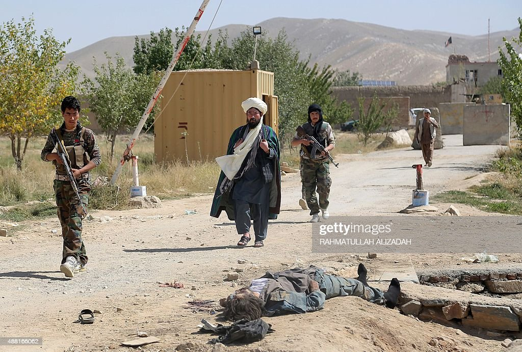Afghan security forces on guard walk past the body of an alleged Taliban insurgent in military uniform in Ghazni on September 14 2015 Taliban...