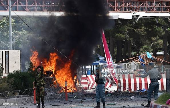 Afghan security forces shout as they keep watch at the site of a huge blast struck near the entrance of Kabul's international airport in Kabul on...