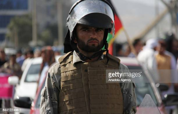 Afghan security forces stand guard during a protest against Myanmar's oppression towards Rohingya Muslims in front of the United Nations' Office in...