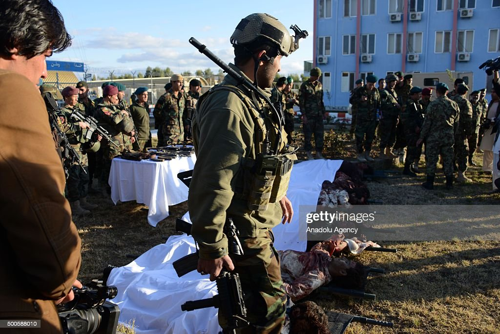 Afghan security forces stand near the dead bodies of Taliban militants who were killed during the clashes in an airfield in Kandahar Afghanistan on...
