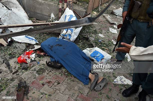 Afghan security forces stand over the body of a woman killed by a car bomb in Kabul on August 22 2015 A suicide car bomb apparently targeting a...