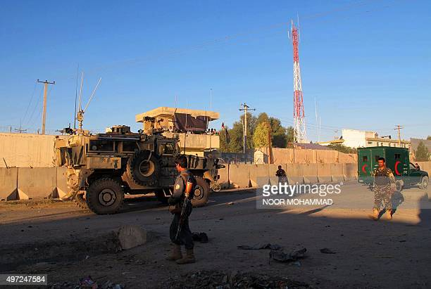 Afghan security forces walk at the scene of a suicide bomb attack that targeted foreign military vehicles in Lashkargah city capital of Helmand...