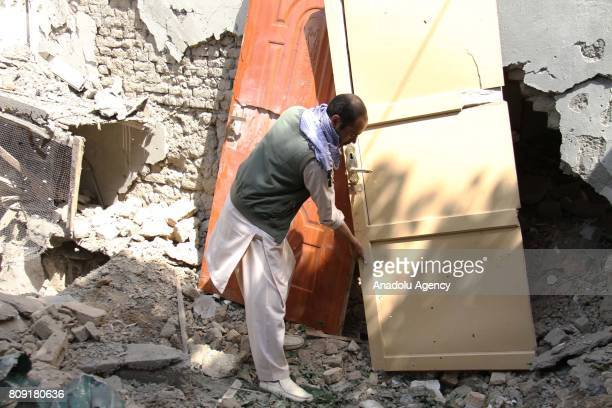 Afghan security officials inspect the house that hit by rockets in Kabul Afghanistan on July 5 2017 A woman and a child were killed as rockets hit...
