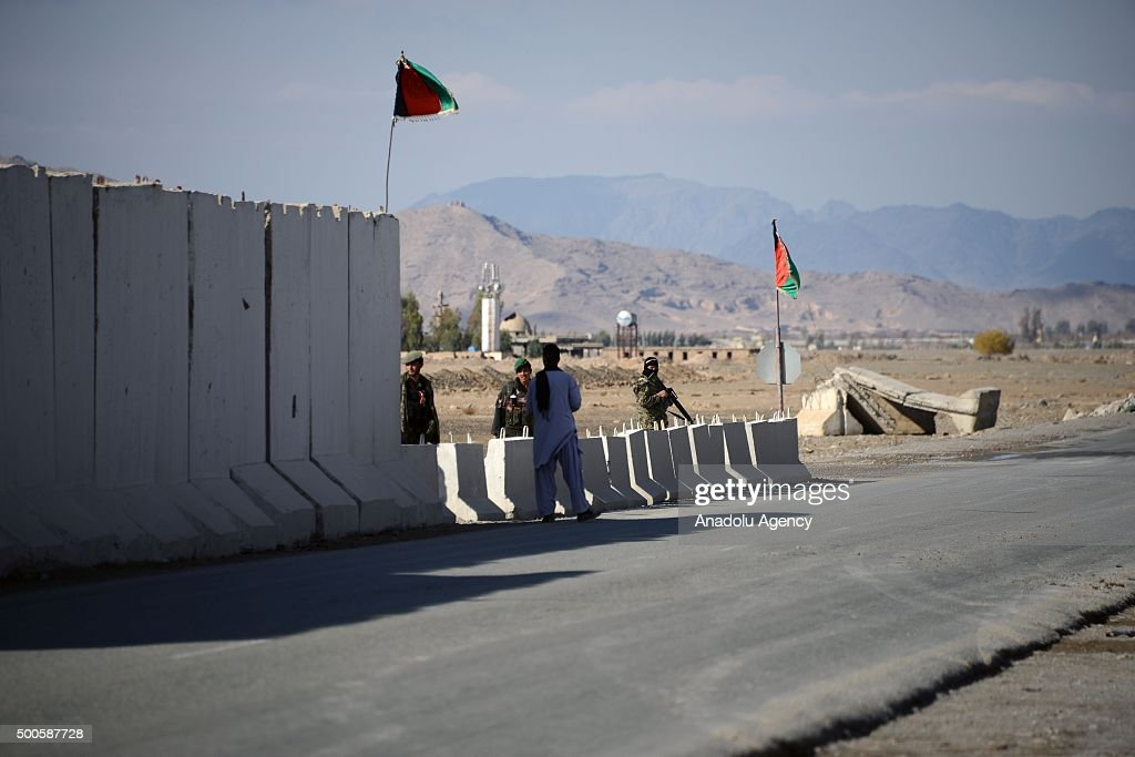Afghan security officials stand guard at an airfield following the clashes between Afghan security forces and Taliban militants in Kandahar...