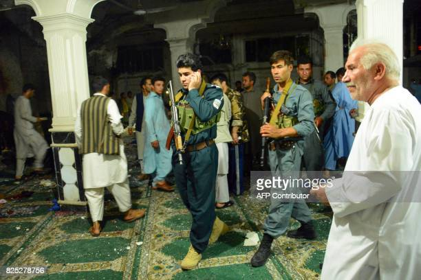 Afghan security personel inspect the site of a suicide bomb attack at a Shiite mosque in Herat on August 1 2017 A suicide bomber and a gunman killed...