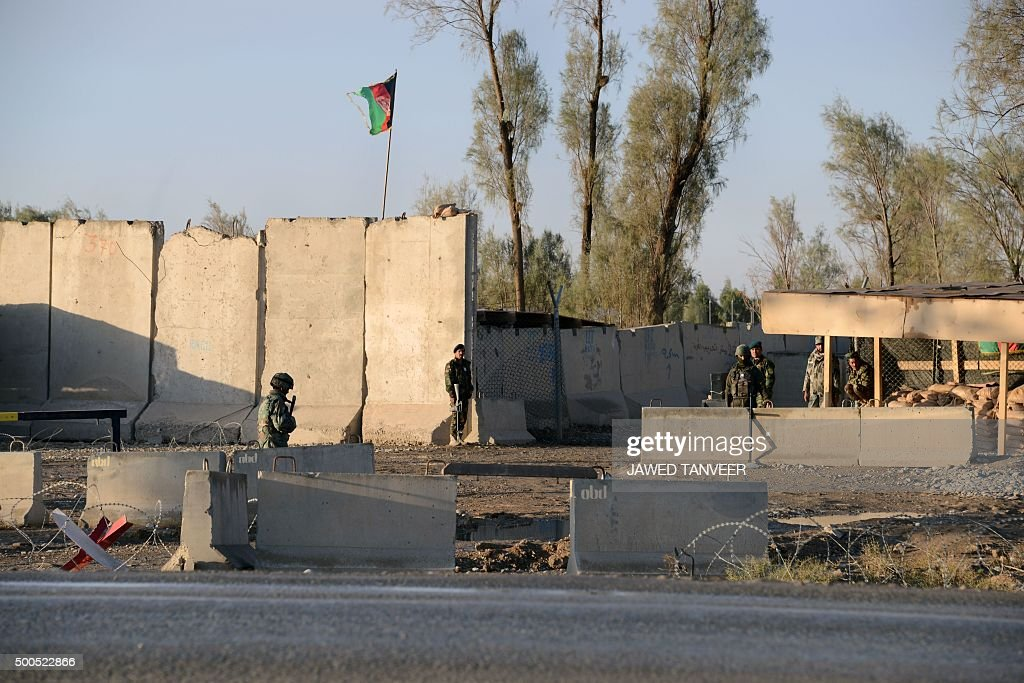 Afghan security personel stand guard near the airport complex in Kandahar on December 9 2015 At least eight people were killed after Taliban...
