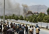 Afghan security personnel and bystanders look on as black smoke billows from the Afghan Parliament building in Kabul on June 22 during an attack in...