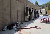 Afghan security personnel and others stand next to a body of a militant after an attack targeted police headquarters in Lashkar Gah on June 30 2015 A...