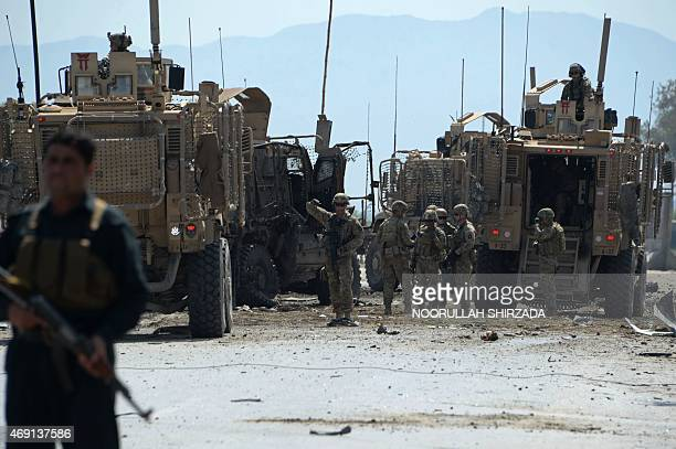 Afghan security personnel and US soldiers inspect the scene of a suicide attack near airport in Jalalabad on April 10 2015 A suicide car bomb...