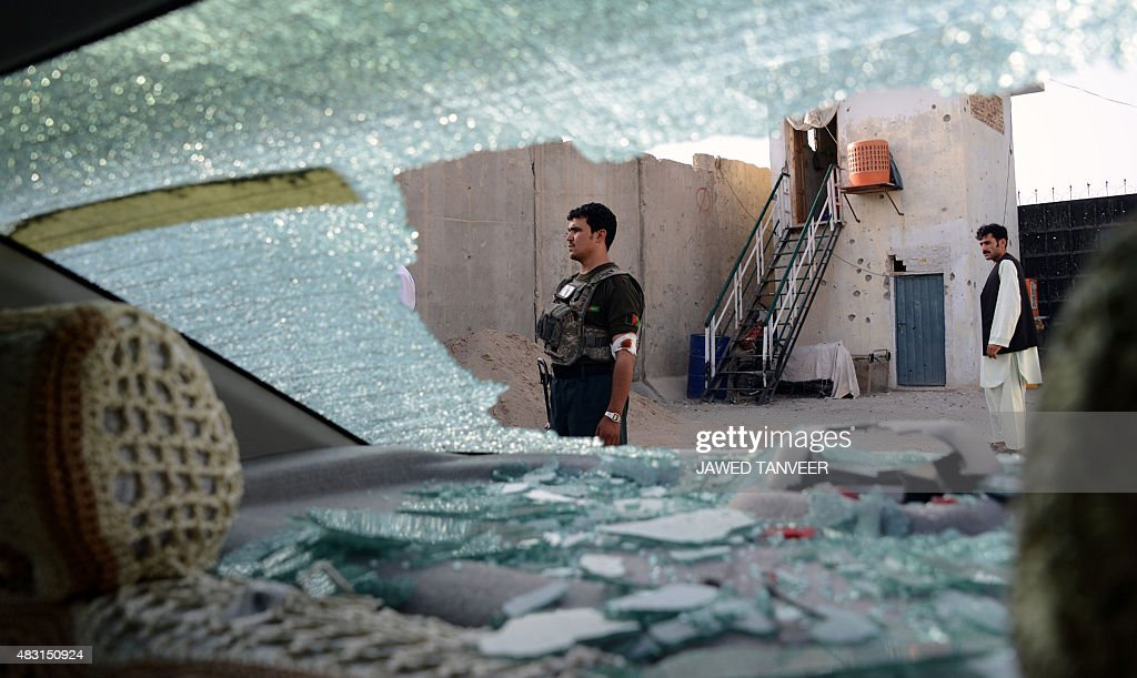 Afghan security personnel are seen through the shattered window of a vehicle as they stand alert at the scene of a Taliban attack in Kandahar on...