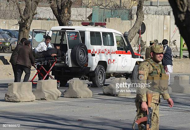 Afghan security personnel carry a victim to an ambulance at the site of a suicide car bomb next to a police base in Kabul on February 1 2016 A...