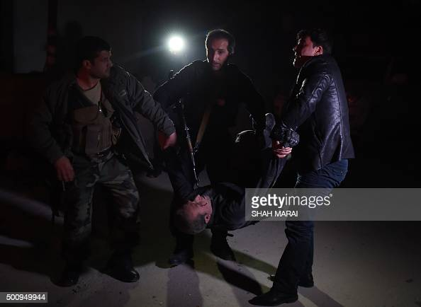 TOPSHOT Afghan security personnel carry a wounded man at the site of an attack on the Spanish embassy compound in Kabul on December 11 2015...