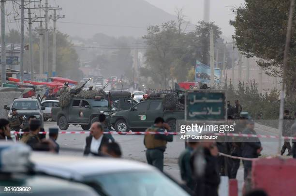 Afghan security personnel gather as they keep watch near the site of a suicide bomb attack near the Marshal Fahim military academy base in Kabul on...
