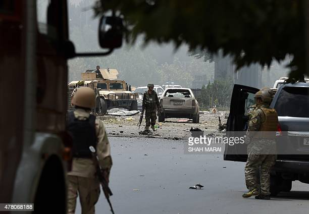 Afghan security personnel gather at the site of an attack in front of The Parliament Building in Kabul on June 22 2015 Taliban militants attacked the...