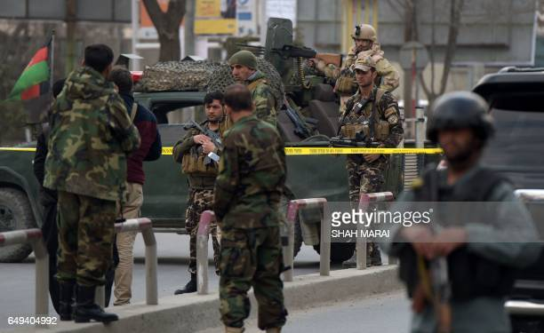 Afghan security personnel gather near the site of an explosion in Kabul on March 8 2017 An explosion and gunfire rattled Kabul's diplomatic district...